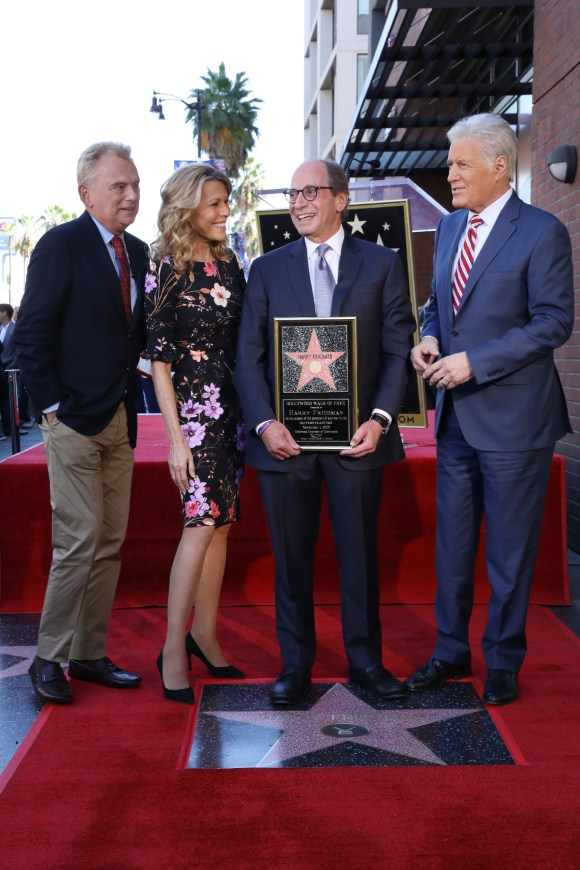 Pat Sajak, Vanna White, Harry Friedman and Alex Trebek stand on a red carpet near Friedman's star on the Hollywood Walk of Fame.