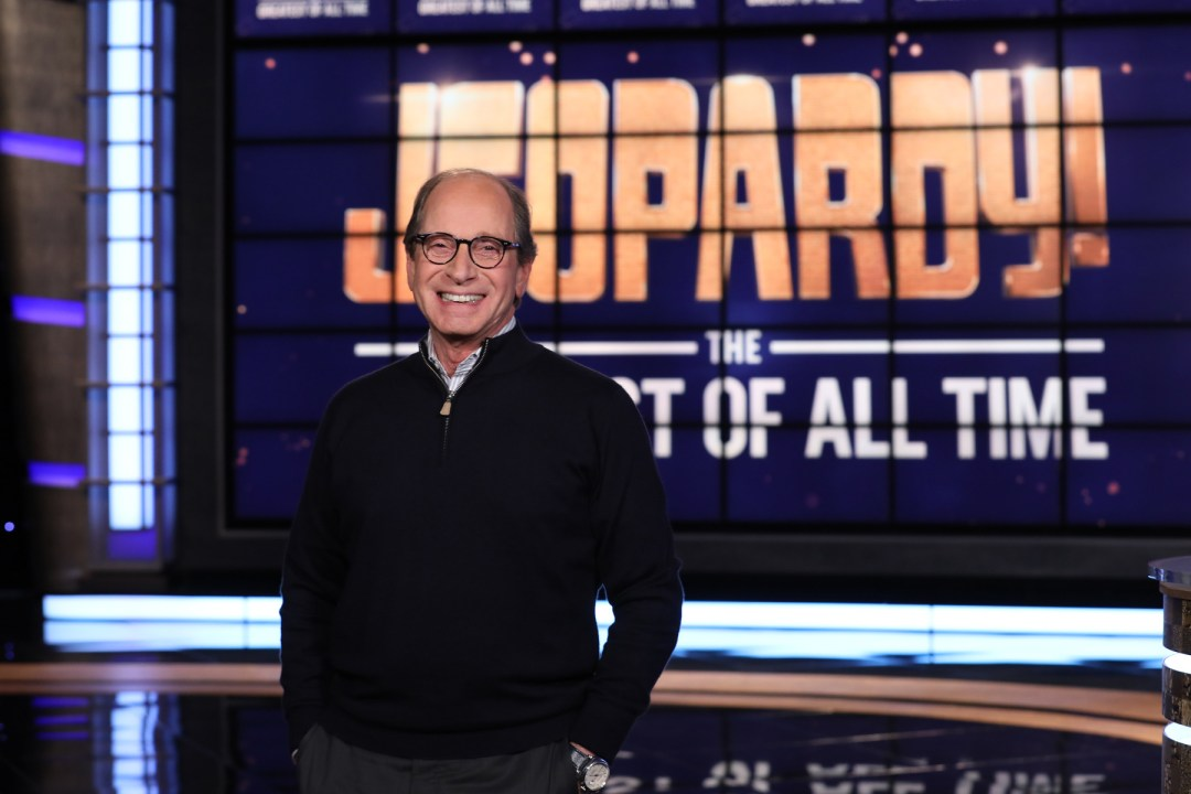 Harry Friedman, standing in front of a Jeopardy! sign