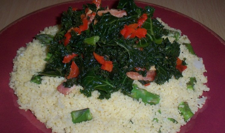 A plate of kale cooked with pepper and bacon, served over couscous