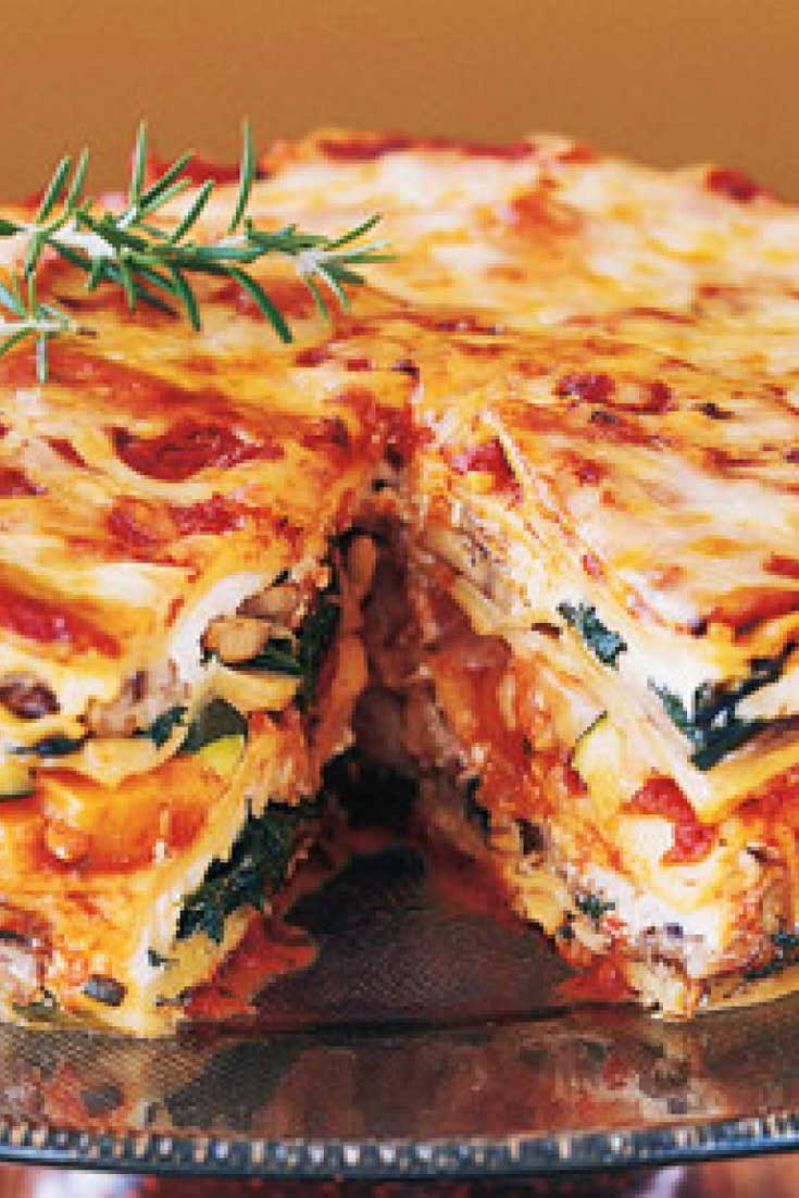 This Mile High Veggie Lasagna Pie is stacked with fresh vegetables, baby greens, aromatic herbs, three kinds of Italian cheeses, and a rich, hearty tomato-basil sauce. It's ideal for a special-occasion dinner. #lasagna #meatlessmonday #vegetarian #dinnerideas