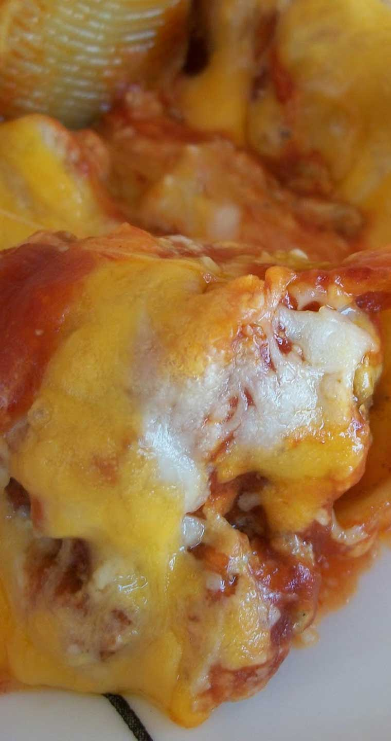 This recipe for Taco Stuffed Shells isn\'t your ordinary stuffed shell recipe but man is it delicious. The meat is mixed with cream cheese, stuffed inside the shell, and topped with taco sauce and cheese. SOOOOO good! #pasta #taco #dinnerideas