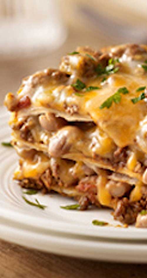 Create a little fusion with ooey-gooey cheese, beans and taco beef layered up and baked like lasagna.