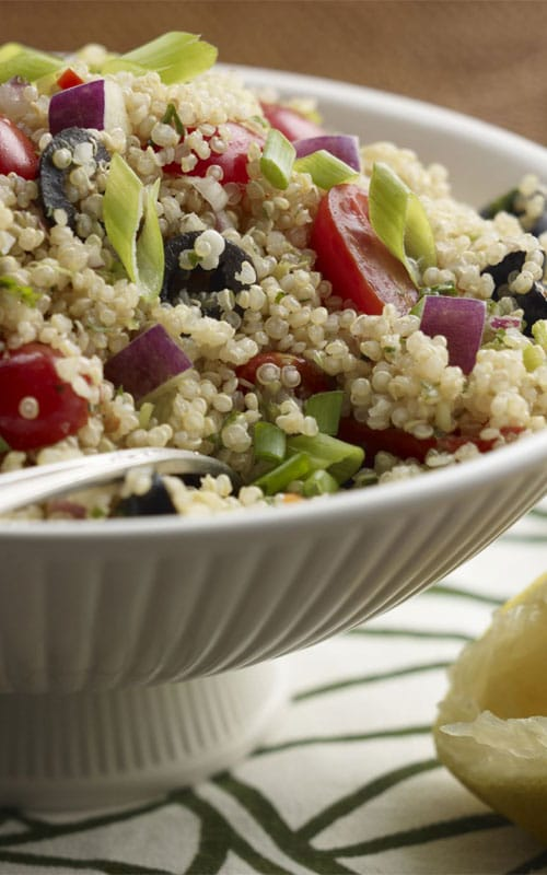 Recipe for Mediterranean Quinoa Salad - What a party of flavor! A tasty side salad featuring quinoa and a colorful variety of vegetables. Feta cheese and a light lemon dressing complete the Mediterranean Quinoa Salad.