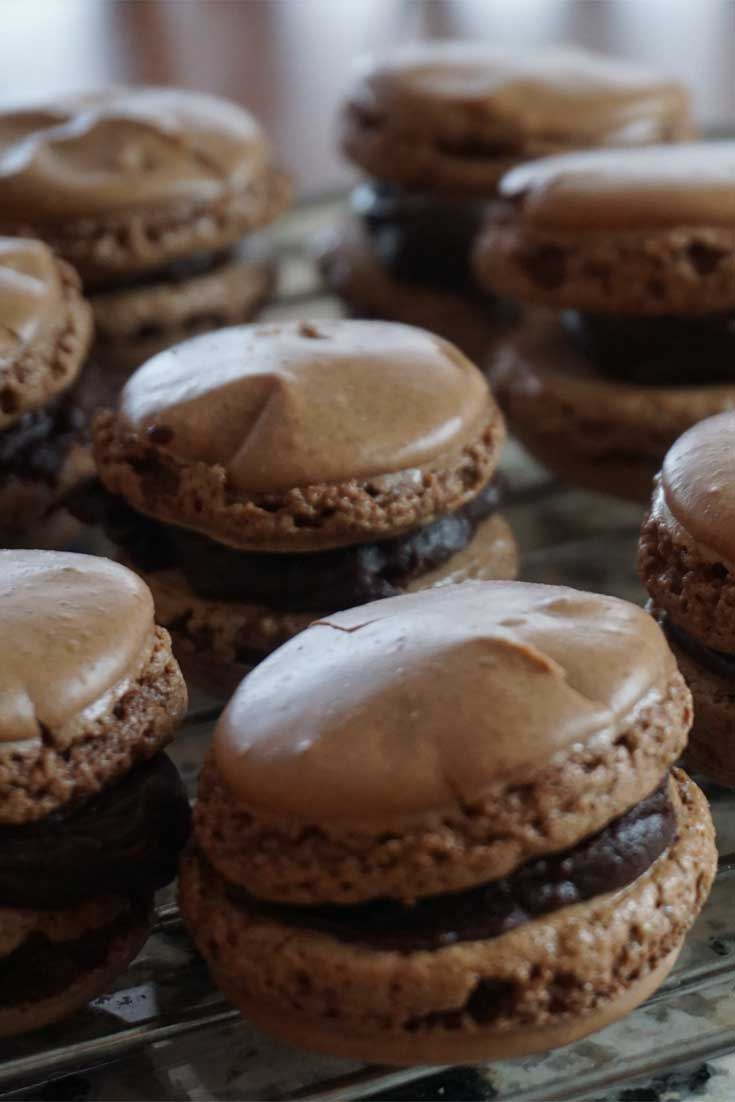 Whip up a batch of these French Chocolate Macarons and pretend that you are taking a trip to Paris. You will fall in love with these crisp chocolate cookies and their luscious creamy ganache filling. #chocolate #cookies #dessert #French