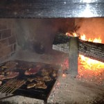 Grilled meats cooking on the fire at L'Ovile Restaurant in Sacrofano