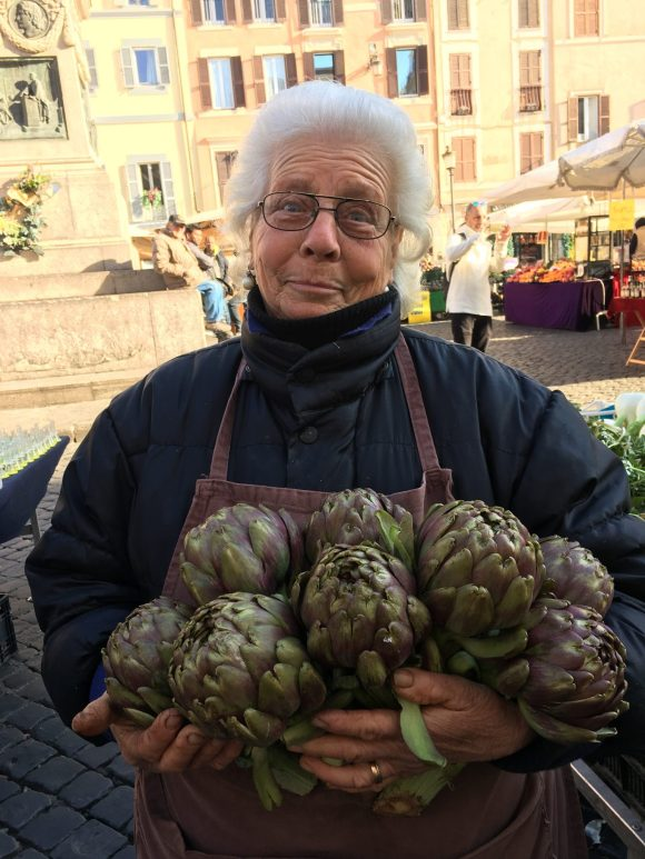 Market lady with artichokes