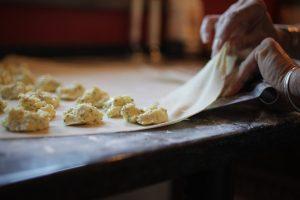 Putting filling on dough for Ravioli Caprese