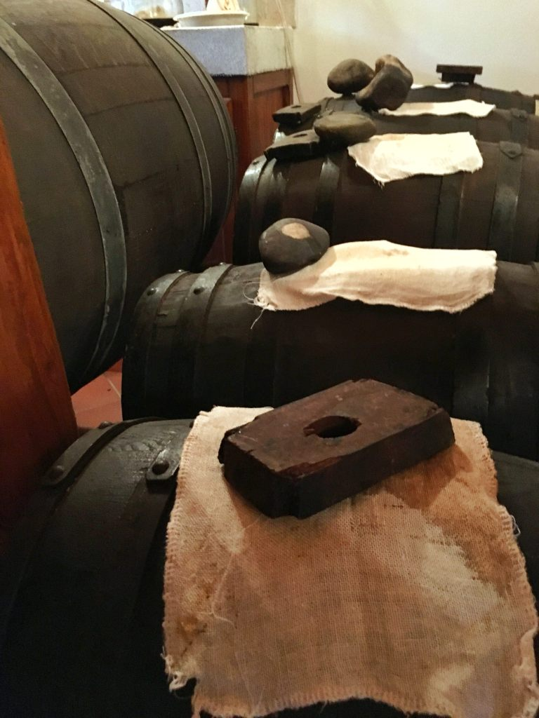 traditional balsamic vinegar barrels are covered with a thin cloth and either a stone or piece of wood placed on top
