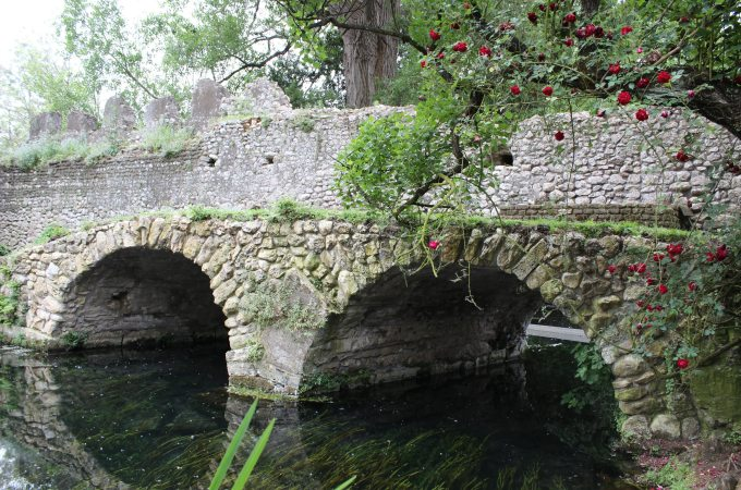 Ruins of an ancient stone bridge in the Ninfa Gardens