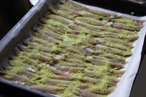 Sprinkle the anchovies with herbed breadcrumbs
