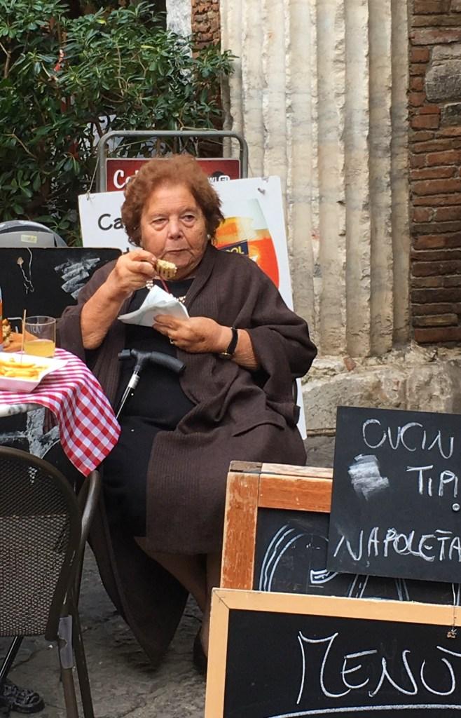 Woman in Naples Italy enjoying a panino at a streetside bar