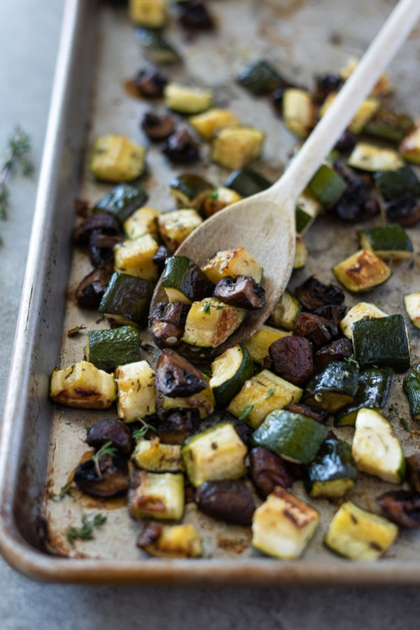 roasted zucchini and mushrooms on a sheet pan with a wooden spoon