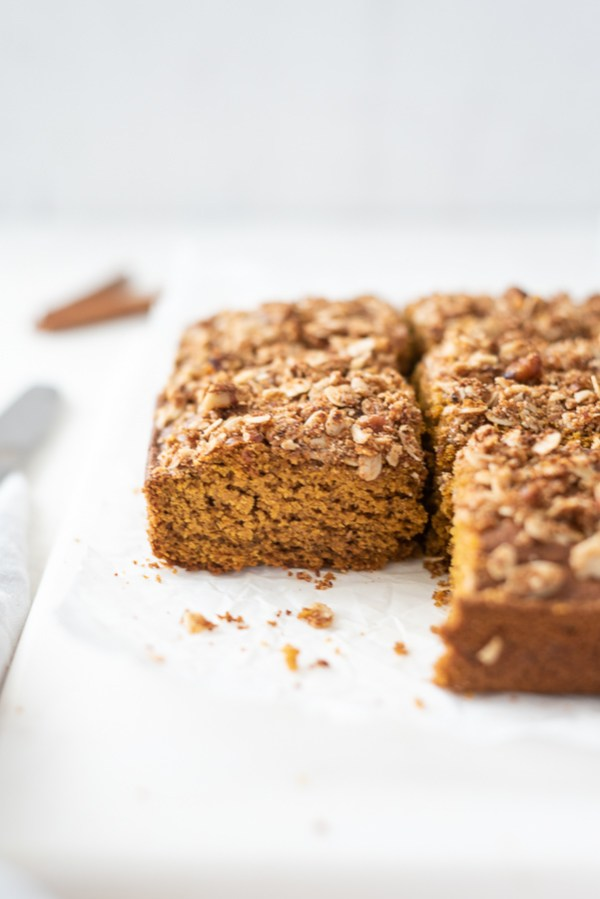 pumpkin coffee cake sliced into squares on a marble board