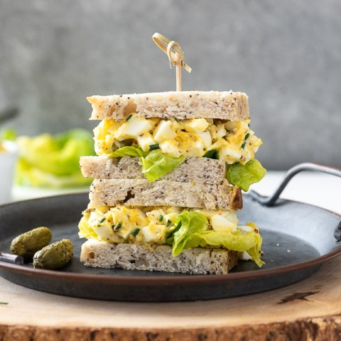 egg salad sandwich piled on a plate with a wooden pick