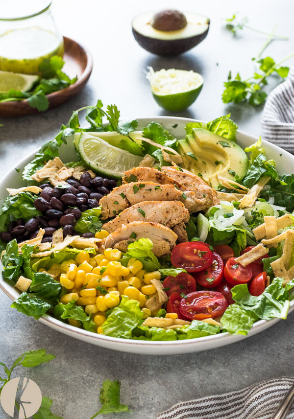 Santa Fe Chicken Salad with Tangy Lime Dressing is a fresh, hearty salad packed with black beans, roasted corn and tortilla strips tossed with a zesty lime dressing! {GF}