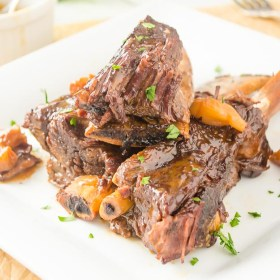 close up of pressure cooker short ribs piled on a white plate