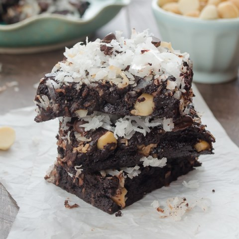 coconut brownies stacked up on parchment paper
