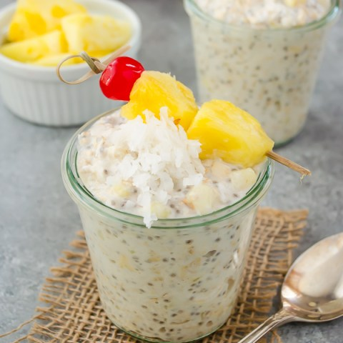 front view of pina colada overnight oats in jar with pinepple, coconut and cherry on top