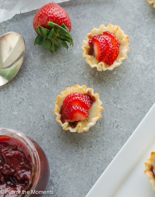 Mini Phyllo Strawberry Brie Bites are crisp phyllo shells filled with strawberry jam, brie cheese, and topped with fresh strawberries. They're the ultimate bites! @FlavortheMoments