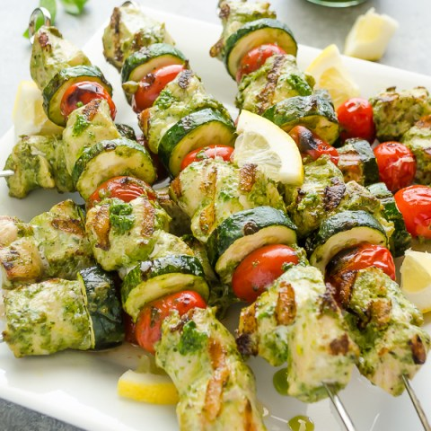 pesto chicken skewers piled on a white plate