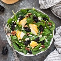 Power green salad with pears and blackberries on a white plate