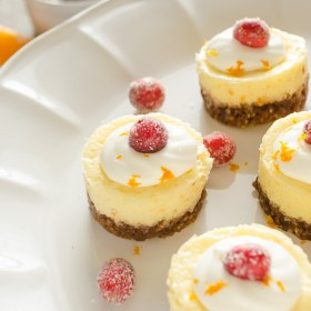 close up of cranberry orange cheesecake with sugared cranberry on top