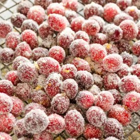 Orange Sugared Cranberries piled on a wire rack with orange zest