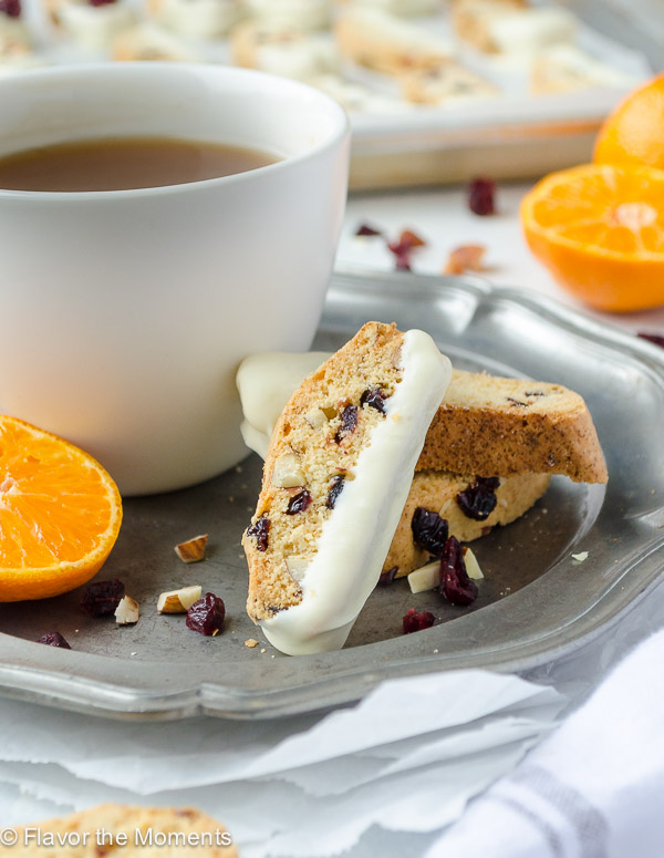 Cranberry Orange Almond Biscotti are crunchy biscotti studded with tart sweet cranberries, toasted almonds, and orange zest. They're dipped in white chocolate and are perfect for tea dunking! @FlavortheMoment