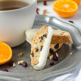 cranberry orange biscotti on plate with cup of tea