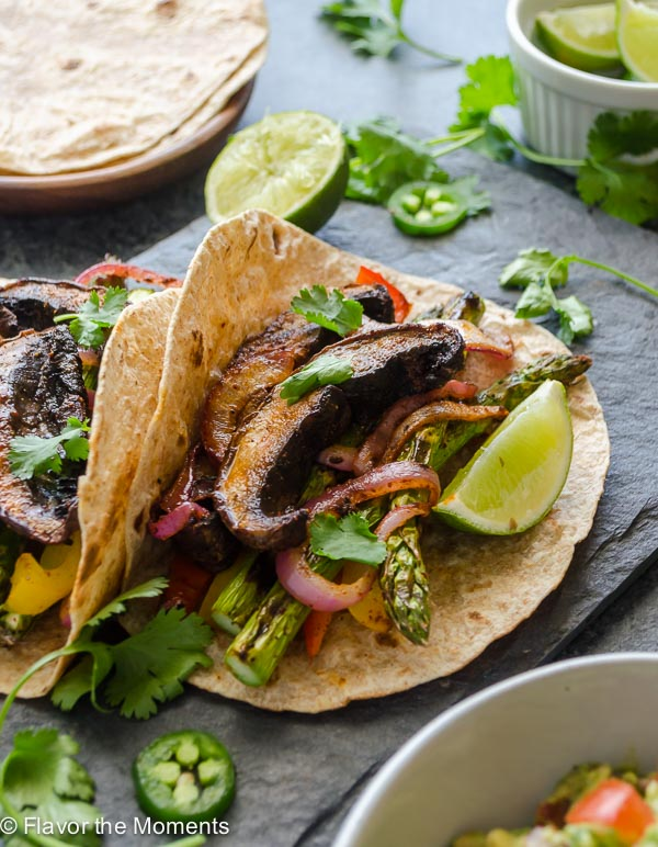 Grilled Portobello Mushroom Asparagus Fajitas are fajita spiced veggies grilled to perfection. Serve with homemade guacamole for a healthy, delicious 30 minute meal! @FlavortheMoment