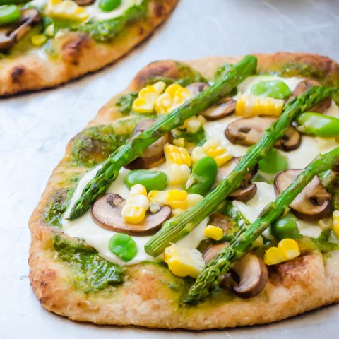 Pesto veggie pizza on baking sheet