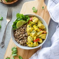 overhead shot of coconut curry chicken on a wooden cutting board with linen and fork