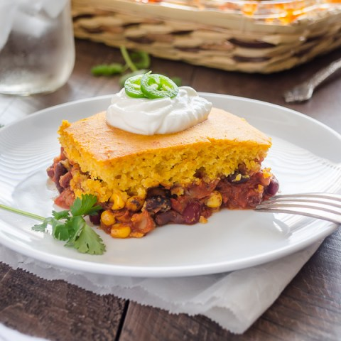 tamale pie on a plate with sour cream and jalapeño on top