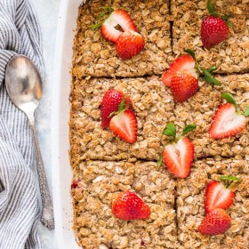 Overnight Strawberry Rhubarb Baked Oatmeal Crisp in white baking dish with sliced strawberries on top