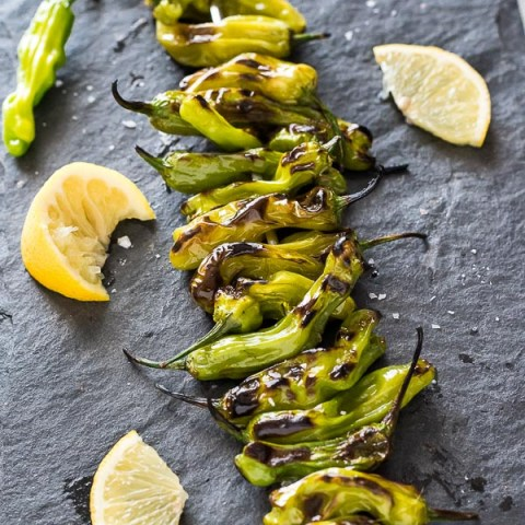 Grilled Shishito Peppers on a skewer with lemon