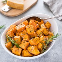 Roasted sweet potatoes in white bowl with rosemary sprigs and spoon
