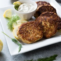 Crispy salmon cakes on white plate with lemon dill sauce