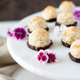 chocolate dipped coconut macaroons front angled view on pedestal