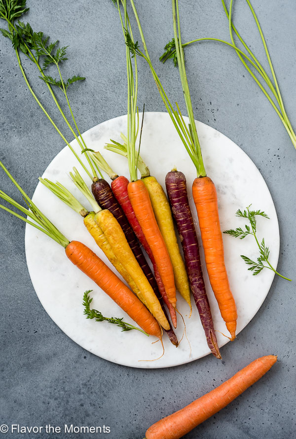overhead angled shot of carrots on a white marble board for carrot produce guide