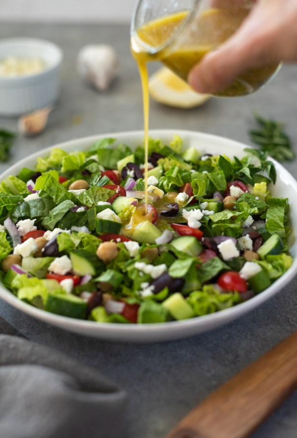 front view of dressing pouring onto Greek chopped salad