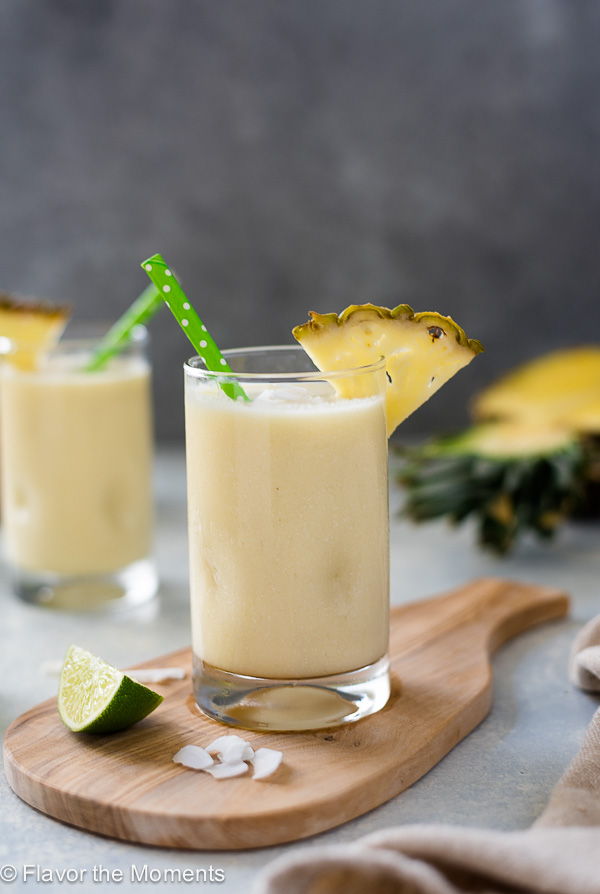 close up front view of pina colada smoothie on a wooden board with green straw and pineapple slice