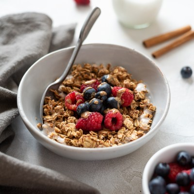 front shot of almond butter granola in bowl with berries and almond butter drizzle