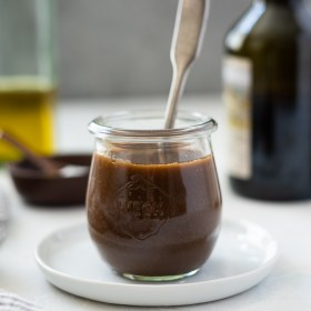 front view of balsamic vinaigrette dressing in a jar with a spoon