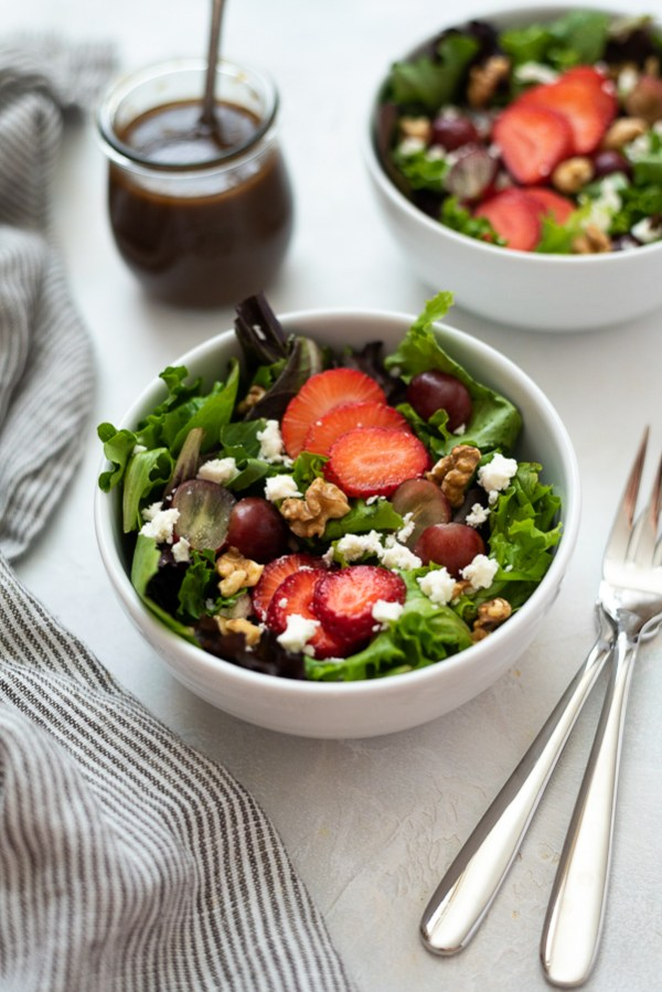 angled overhead shot of strawberry salad in white bowl with forks alongside