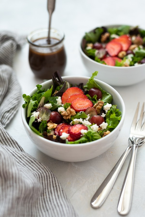 front view of strawberry salad in white bowl with dressing in background