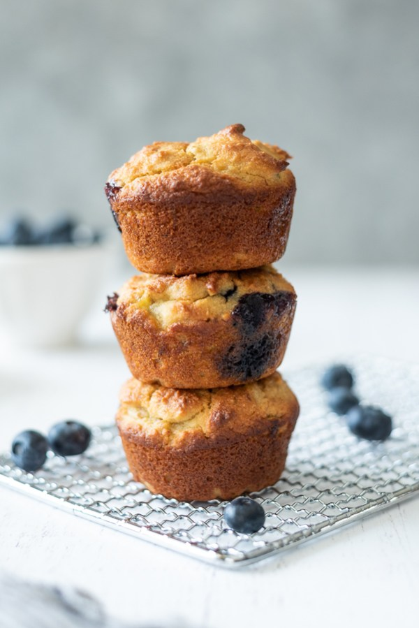 3 almond flour blueberry banana muffins stacked up with blueberries around them