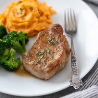 White plate with oven baked pork chop, broccoli and mashed sweet potatoes