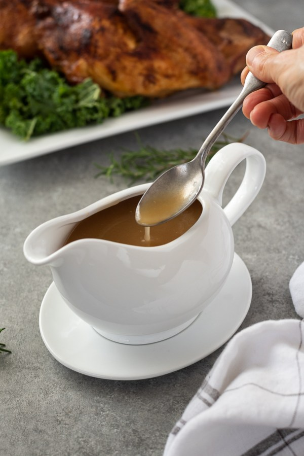 turkey gravy recipe with spoon pouring gravy into gravy boat