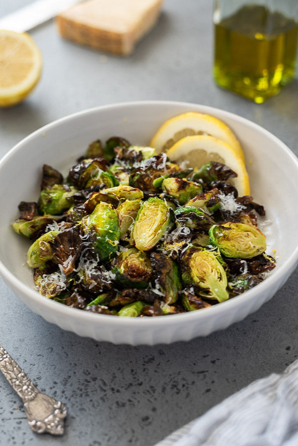 front shot of air fryer brussels sprouts in white serving bowl with lemon and parmesan