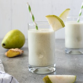 pear smoothie with slice of pear on the top of the glass and green striped straw